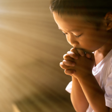 Child praying with hands clasped and closed eyes